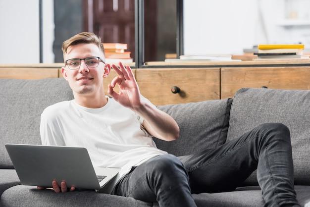 Retrato sonriente de un hombre joven que miente en el sofá que sostiene el ordenador portátil disponible que muestra la muestra aceptable