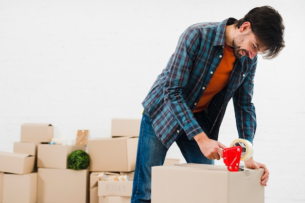 Retrato sonriente de un hombre joven que sella la caja de cartón con cinta adhesiva
