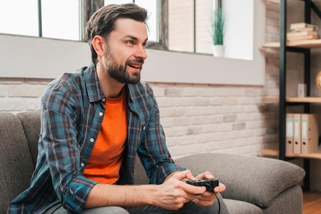 Retrato sonriente de un hombre joven que se sienta en el sofá que juega al videojuego