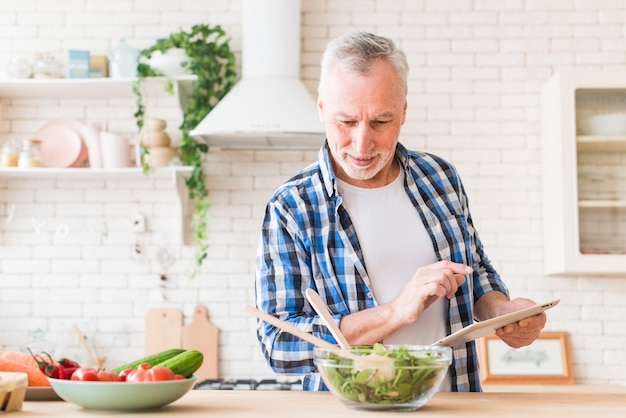 Retrato sonriente del hombre mayor que prepara la comida usando la tableta digital en la cocina