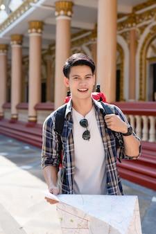 Retrato sonriente hombre mochilero asiático sosteniendo un mapa de papel en la mano en el hermoso templo tailandés