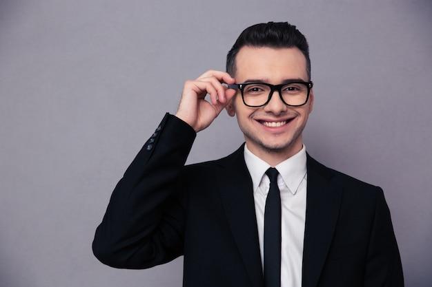 Retrato, de, un, sonriente, hombre de negocios, en, anteojos, encima, pared gris
