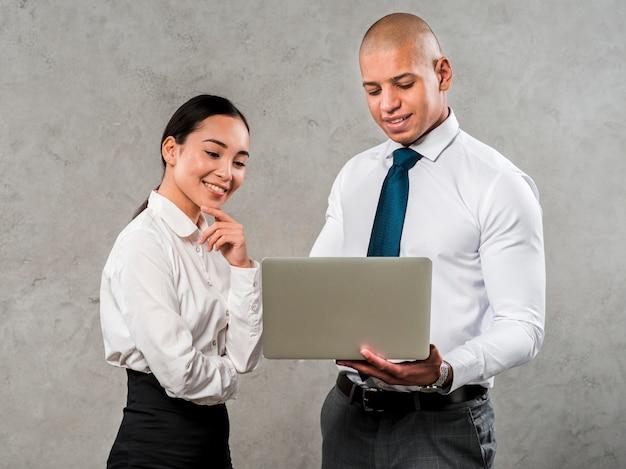 Retrato sonriente de un hombre de negocios y de una empresaria jovenes que miran el ordenador portátil