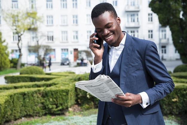 Retrato sonriente de un hombre de negocios joven que habla en el teléfono móvil que lee el periódico