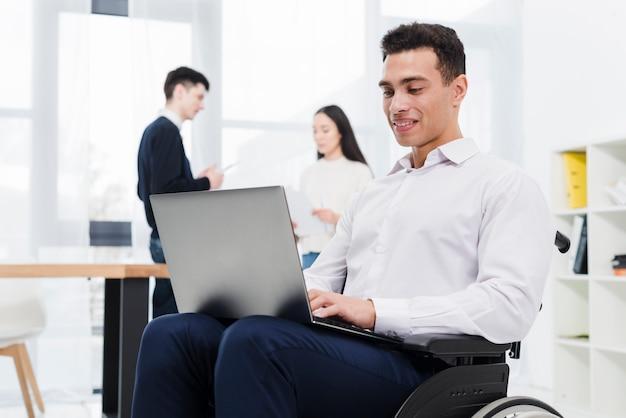 Retrato sonriente de un hombre de negocios joven que se sienta en la silla de ruedas usando el ordenador portátil con su colega en el fondo