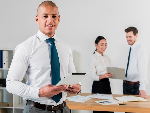 Retrato sonriente de un hombre de negocios joven que sostiene la tableta digital disponible y su colega que trabaja en el fondo