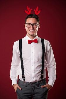 Retrato de sonriente hombre nerd con cuernos de navidad