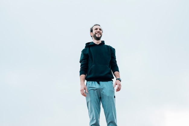 Retrato sonriente de un hombre de pie contra el cielo azul