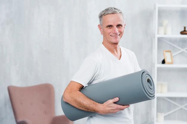 Retrato sonriente de un hombre que sostiene la estera rodada de la yoga en casa