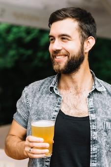 Retrato sonriente del hombre que sostiene el vidrio de cerveza