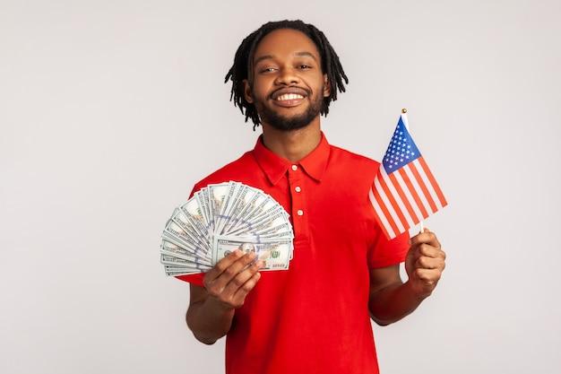 Retrato de sonriente hombre satisfecho sosteniendo la bandera americana y billetes de dólares, celebrando el éxito.