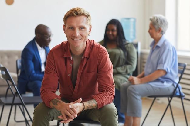 Retrato de sonriente hombre tatuado durante la reunión del grupo de apoyo con personas en la superficie, espacio de copia