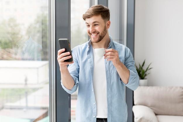 Retrato sonriente hombre usando móvil