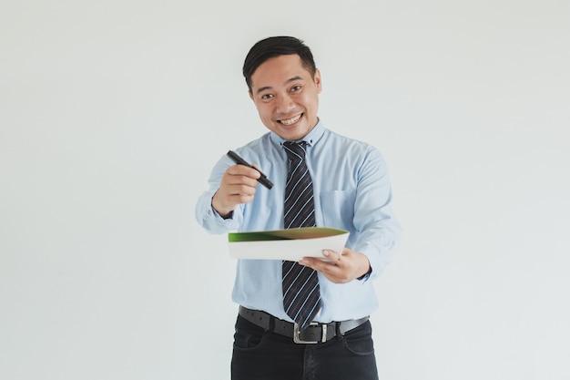 Retrato de sonriente hombre de ventas vestido con camisa azul y corbata extendiendo la mano mientras sostiene una pluma y una carta de acuerdo para firmar en la cámara