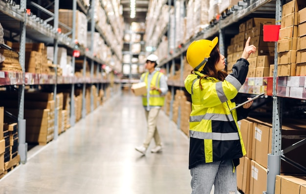 Retrato de sonriente ingeniero asiático en cascos detalles de pedido de mujer en tableta para verificar bienes y suministros en estantes con antecedentes de mercancías en almacén.exportación logística y comercial