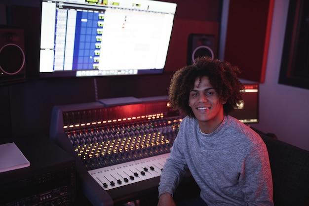 Retrato de sonriente ingeniero de audio masculino