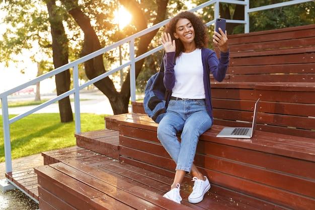 Retrato de una sonriente joven africana con mochila descansando en el parque, tomando un selfie, agitando la mano