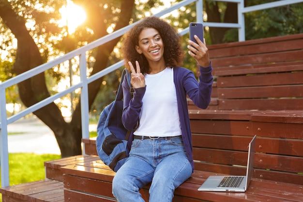 Retrato de una sonriente joven africana con mochila descansando en el parque, tomando un selfie