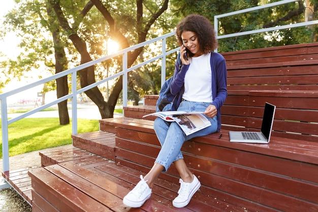 Retrato de una sonriente joven africana con mochila hablando por teléfono móvil mientras descansa en el parque, leyendo una revista
