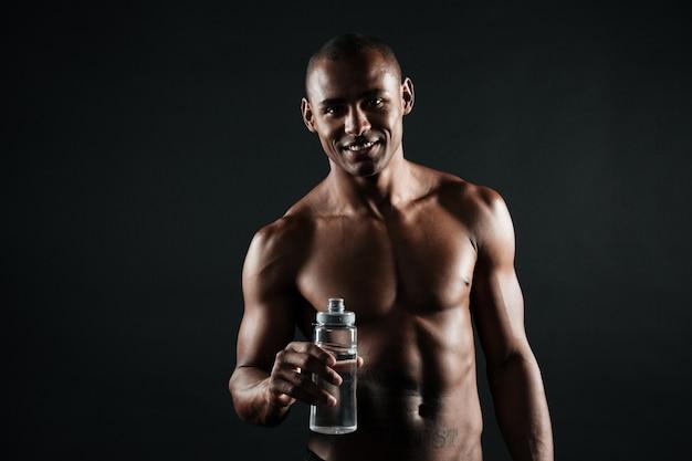 Retrato de sonriente joven afroamericano deportista, sosteniendo una botella de agua