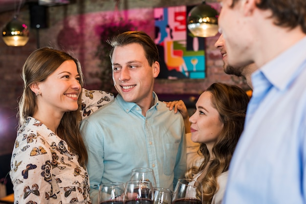Retrato de un sonriente joven amigos disfrutando de fiesta en bar