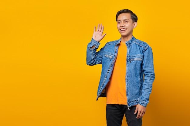 Retrato de sonriente joven asiático saludo espacio vacío sobre fondo amarillo
