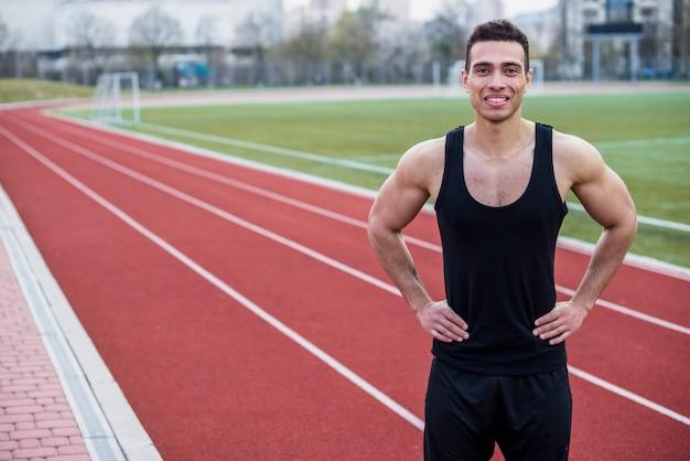 Retrato de un sonriente joven atleta masculino de pie en la pista de carreras