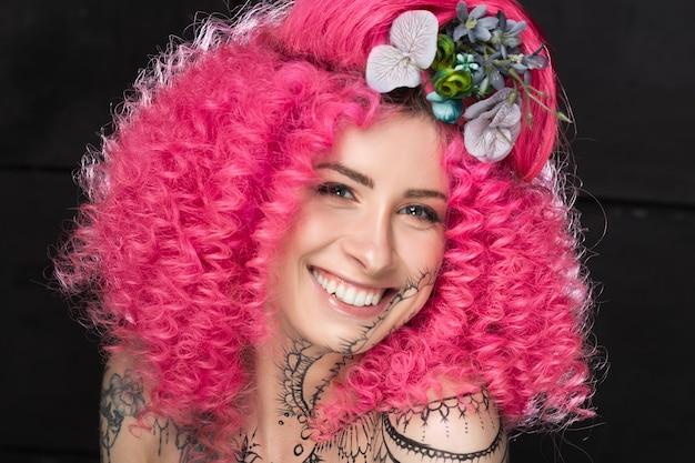 Retrato de sonriente joven atractiva modelo de niña caucásica con estilo afro rizado cabello rosa brillante