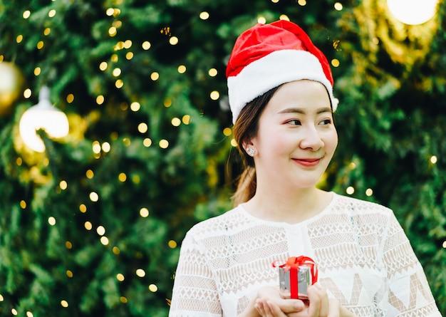Retrato de sonriente joven y bella mujer asiática con regalo en la feria navideña