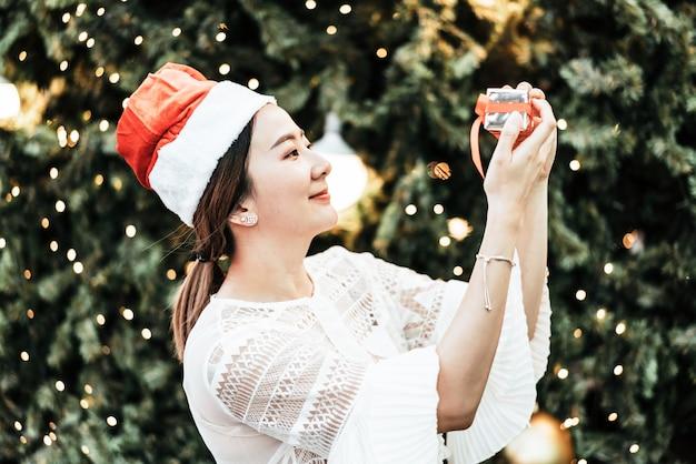 Retrato de sonriente joven y bella mujer asiática con regalo en la festiva feria de navidad