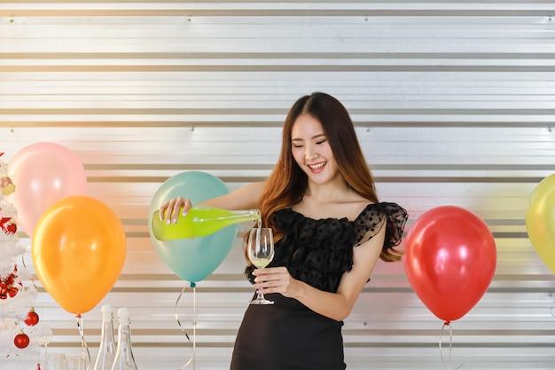 Retrato de sonriente joven y bella mujer asiática con vaso de refresco verde sparkng y botella con fiesta de globos coloridos
