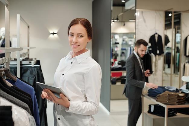 Retrato de sonriente joven y bella vendedora en camisa de pie en el estante y comprobar la recepción de mercancías en la tienda de ropa