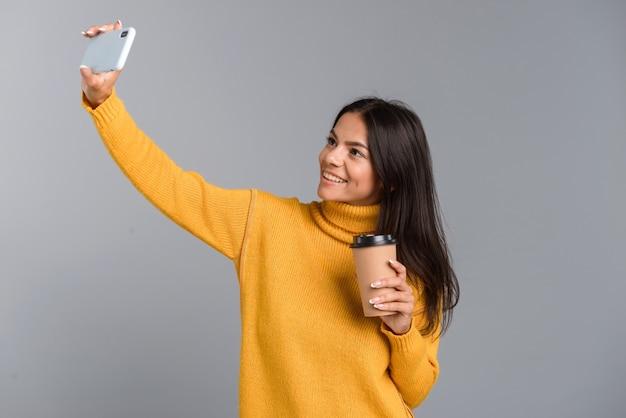 Retrato de una sonriente joven casual aislada sobre pared gris, sosteniendo café para llevar, tomando un selfie con teléfono móvil