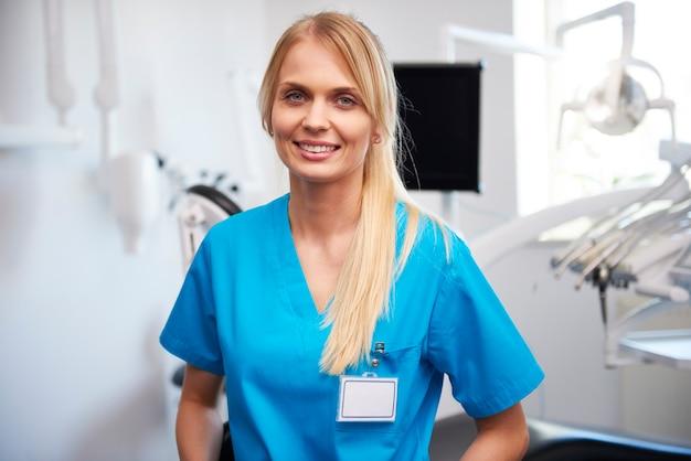 Retrato de sonriente, joven dentista en la clínica del dentista