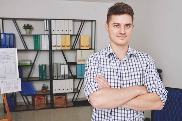 Retrato de sonriente joven diseñador ux seguro de pie en la oficina con los brazos cruzados y mirando al frente