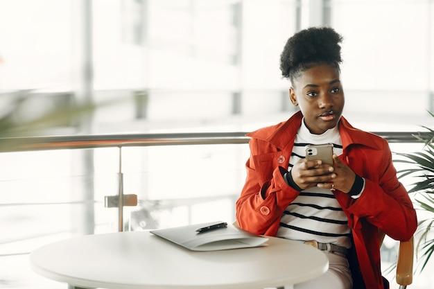 Retrato de sonriente joven empresaria sentado en la oficina