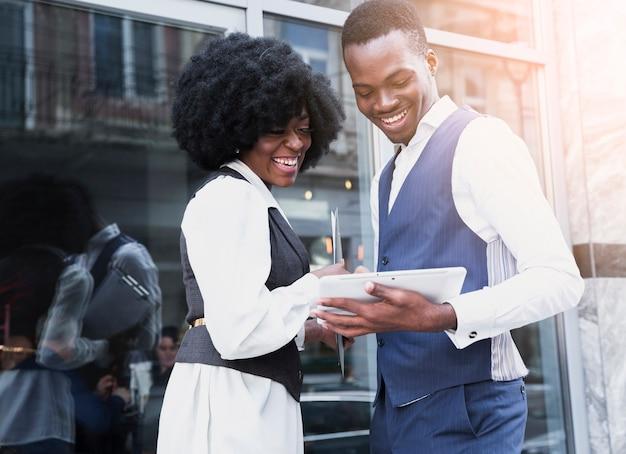 Retrato de un sonriente joven empresario africano y empresaria mirando tableta digital