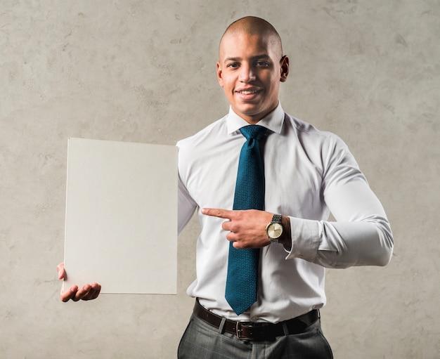 Retrato sonriente de un joven empresario apuntando su dedo hacia un cartel en blanco