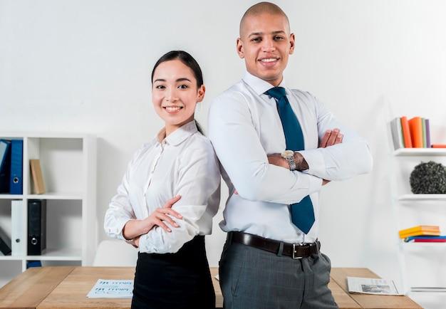 Retrato sonriente de un joven empresario y empresaria de pie de espaldas en la oficina