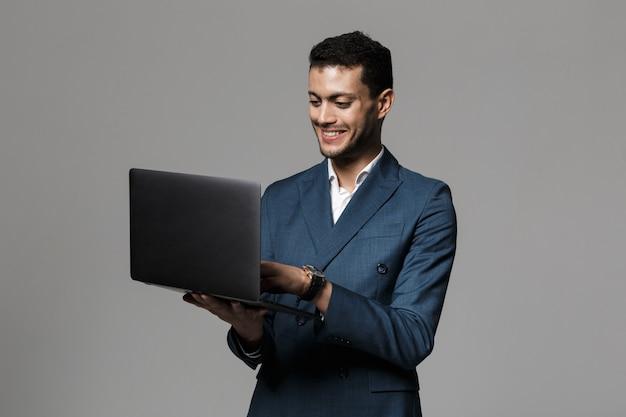 Retrato de un sonriente joven empresario vestido con traje que se encuentran aisladas sobre la pared gris, utilizando equipo portátil