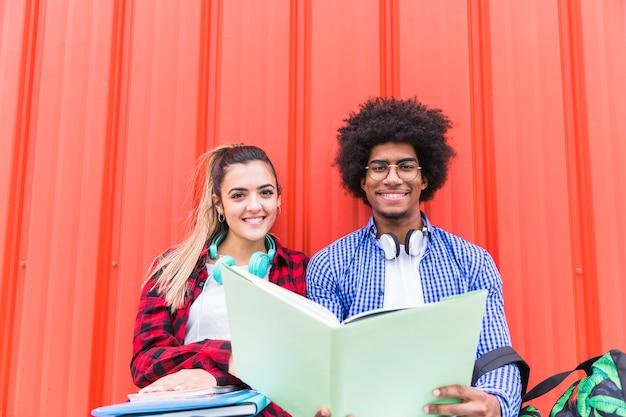Retrato sonriente de un joven estudiante masculino y femenino estudiando juntos