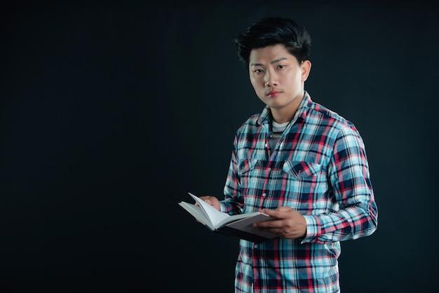 Retrato de sonriente joven estudiante universitario con libros