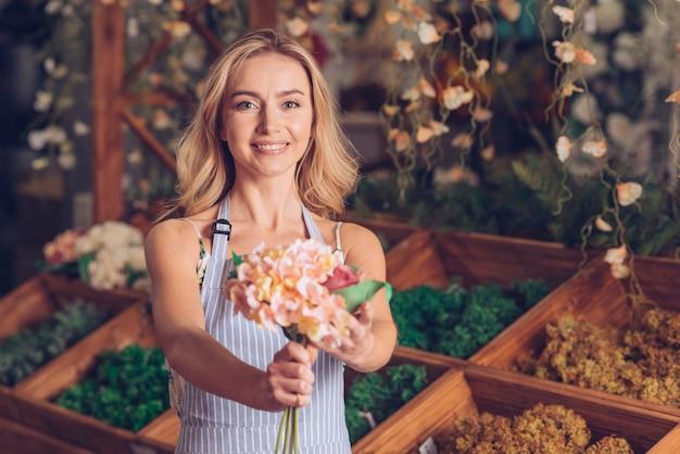 Retrato de sonriente joven mujer florista ofreciendo las flores