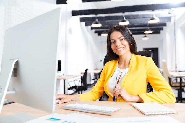 Retrato, de, un, sonriente, joven, mujer de negocios, usar la computadora portátil, en, oficina