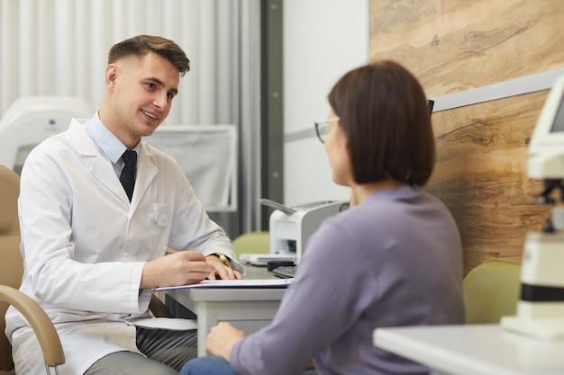 Retrato de sonriente joven oftalmólogo hablando con paciente durante la consulta en la clínica