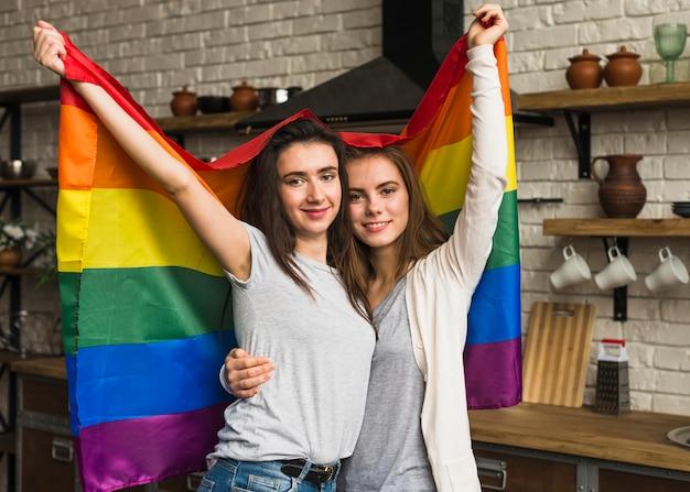 Retrato sonriente de una joven pareja de lesbianas sosteniendo la bandera del arco iris en la mano