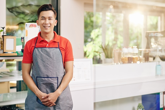 Retrato de sonriente joven propietario de coffeeshop vietnamita de pie en el mostrador