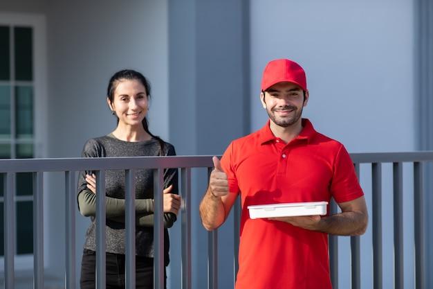 Retrato sonriente joven repartidor en uniforme rojo sosteniendo una caja en frente de la casa.
