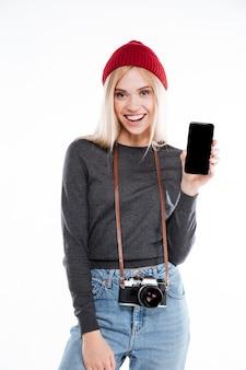 Retrato de una sonriente joven rubia fotógrafo mostrando teléfono móvil