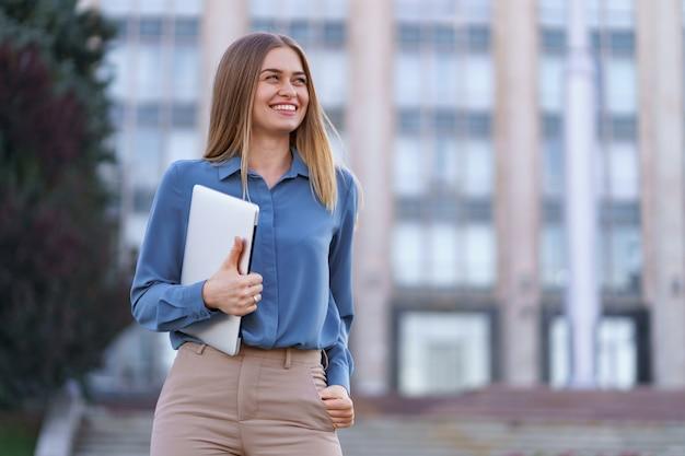Retrato sonriente joven rubia vistiendo la camiseta azul suave sobre edificio